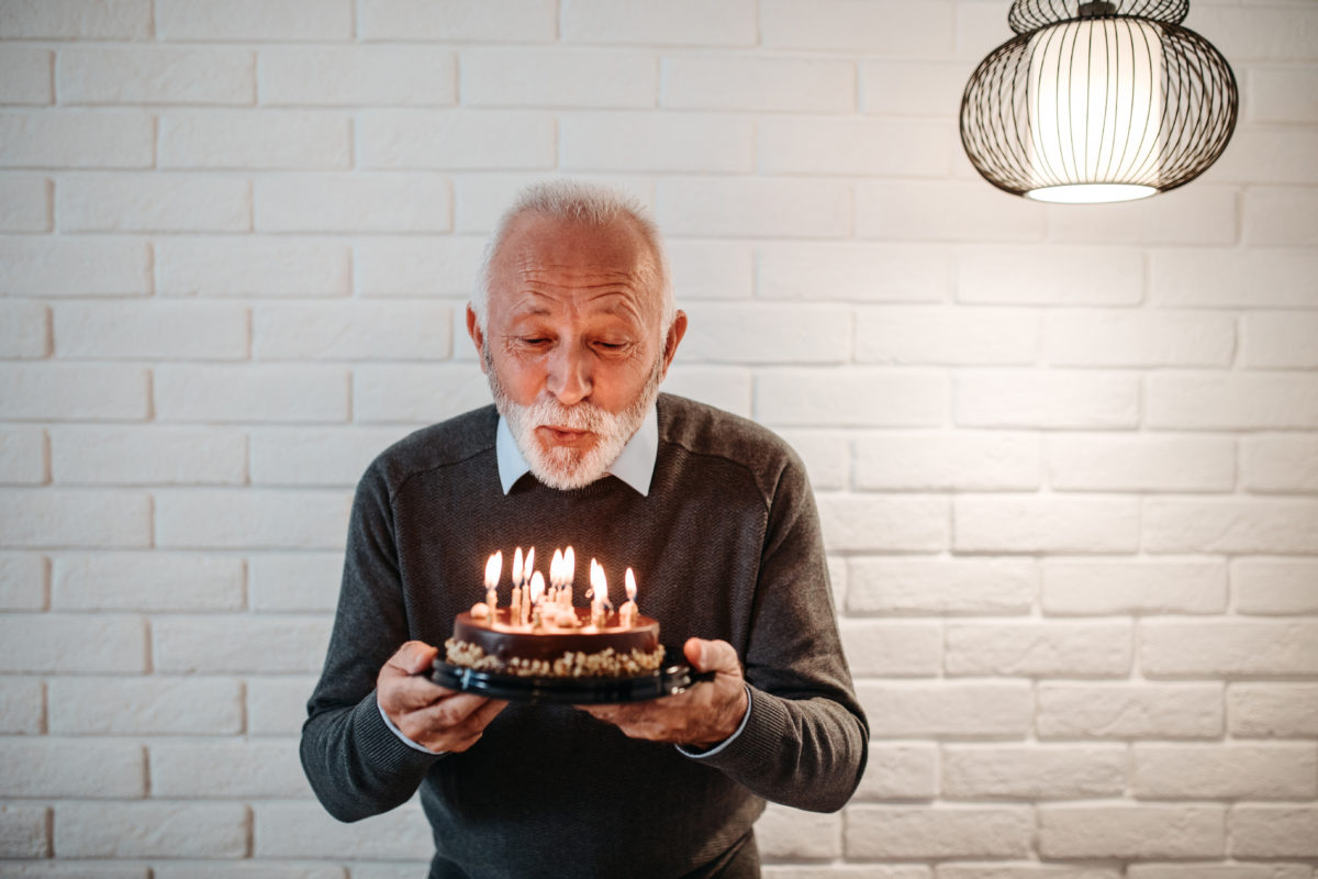 A senior blowing out candles on a cake