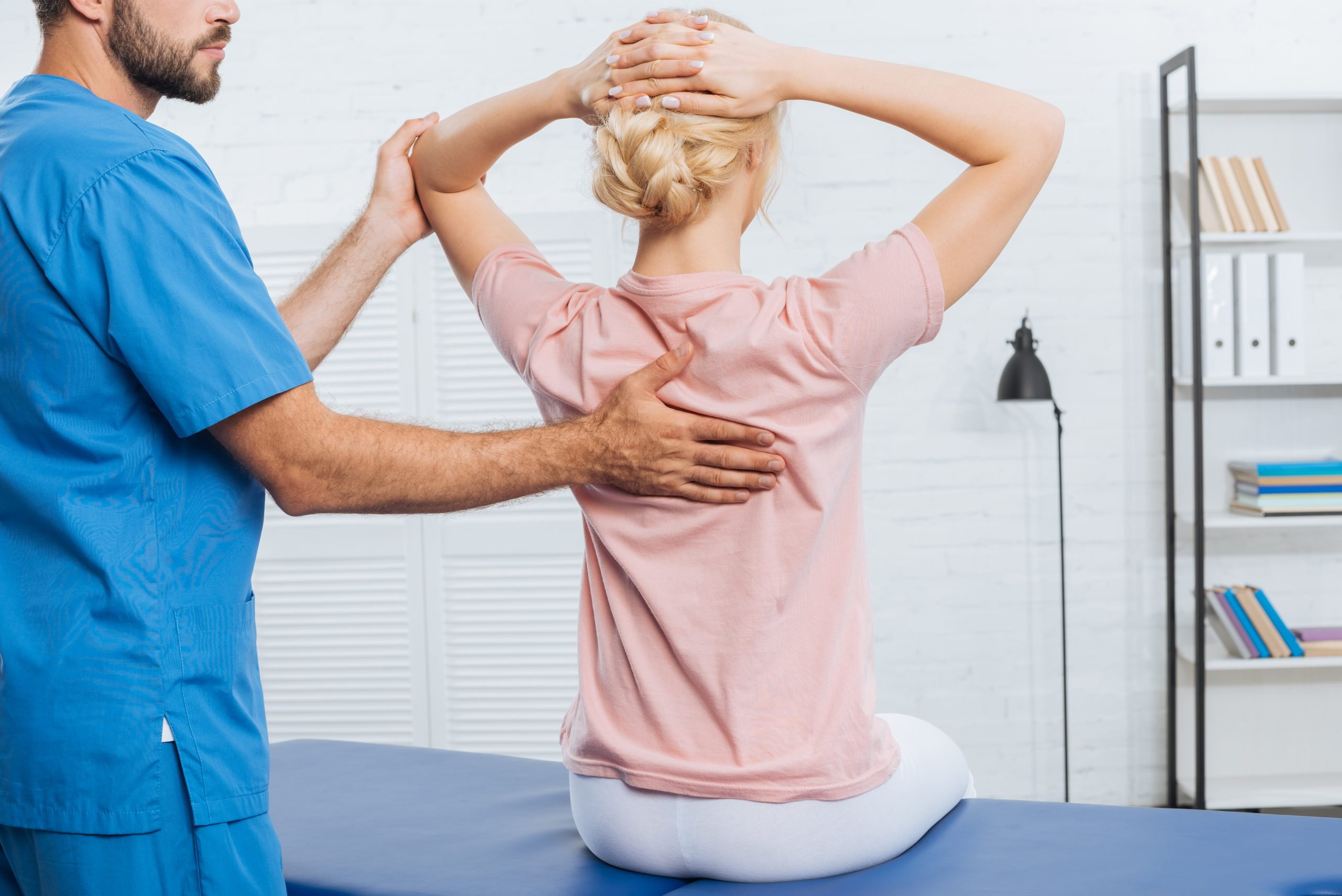a physical therapist helping a young woman with assisted stretch