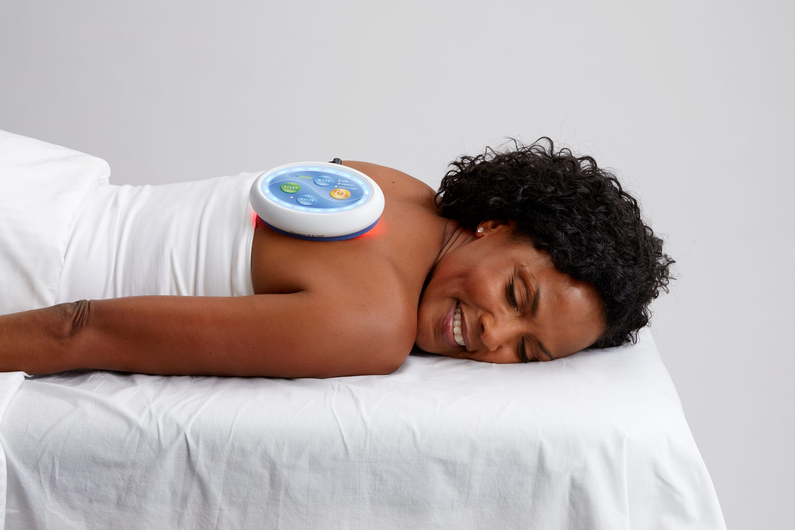 A woman laying on a table with a cellumaPhotobiomodulation Therapy device on her back