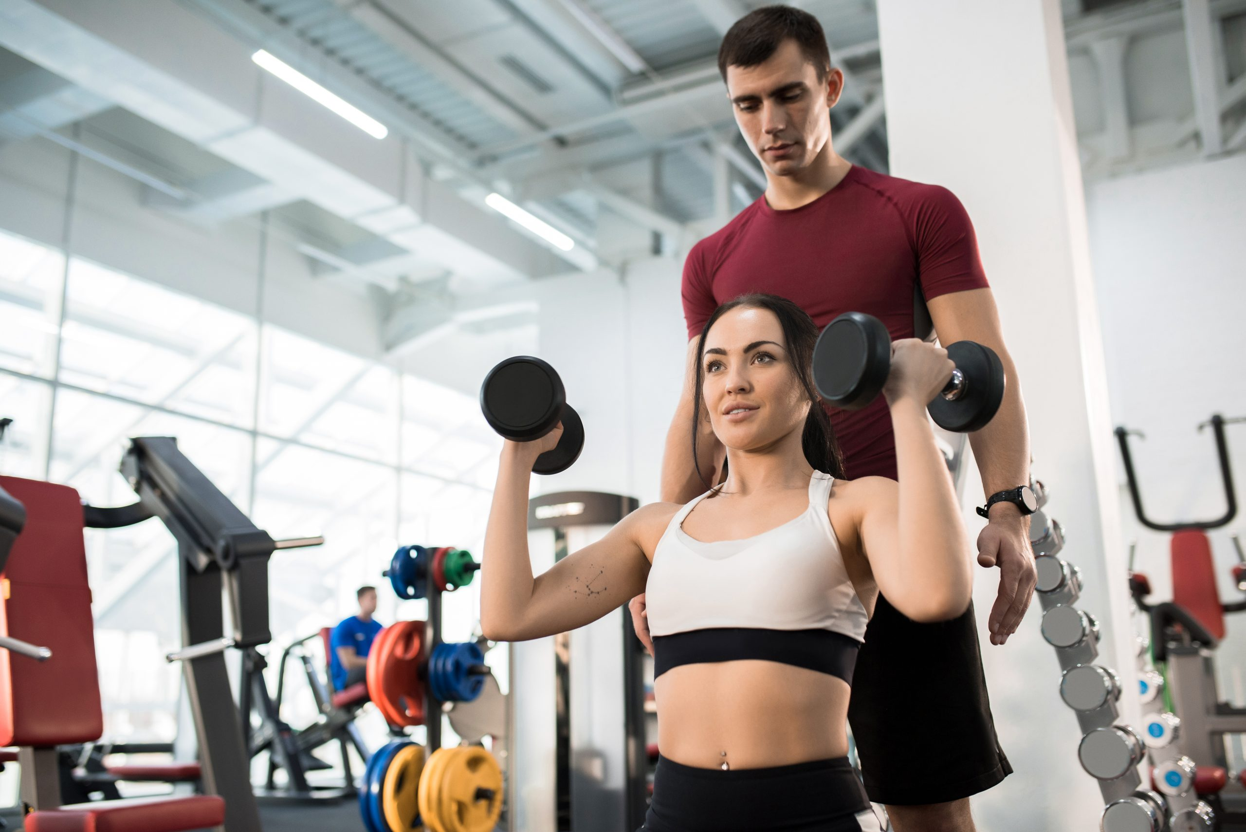 a trainer helping a woman lift weights for a strength and conditioning routine