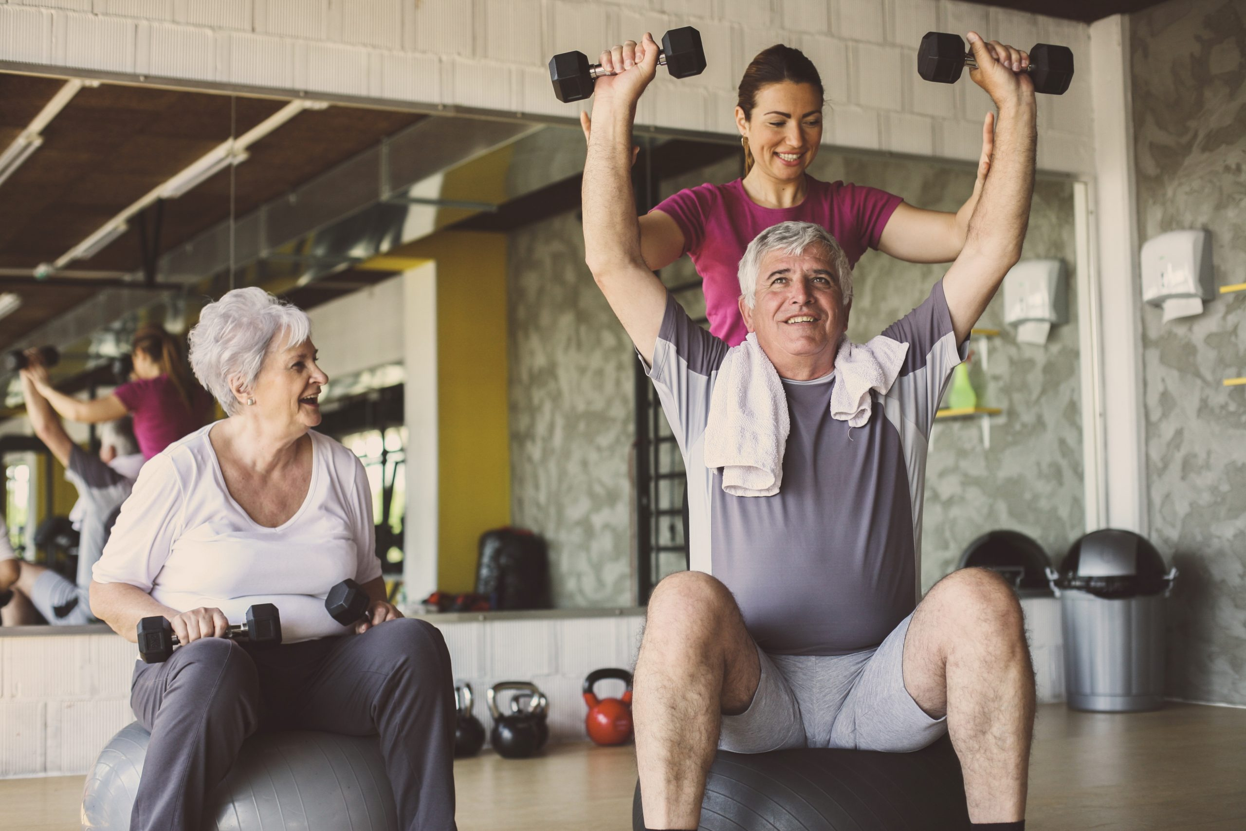 a young trainer helping two seniors with weights