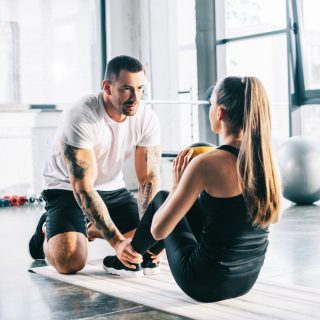 a man helping a woman with strength and conditioning exercises