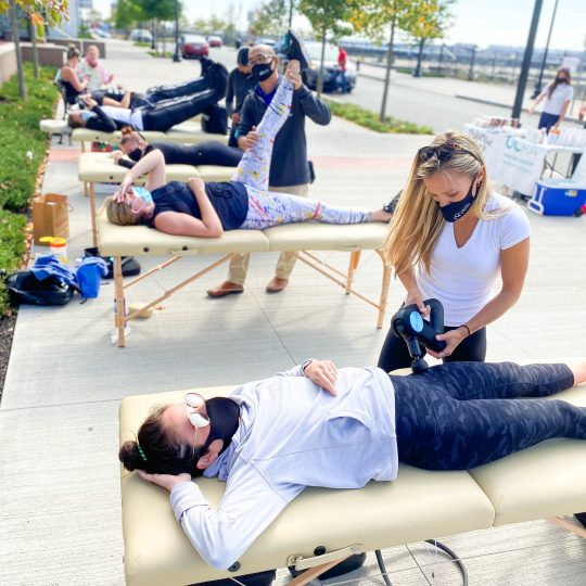 lcg boston DPTs applying various therapy techniques including percussion massage