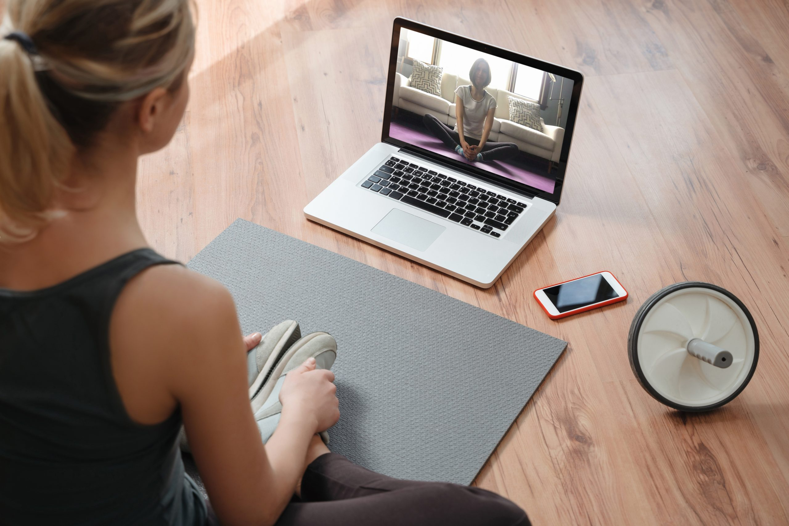 a woman taking a virtual yoga pt lesson