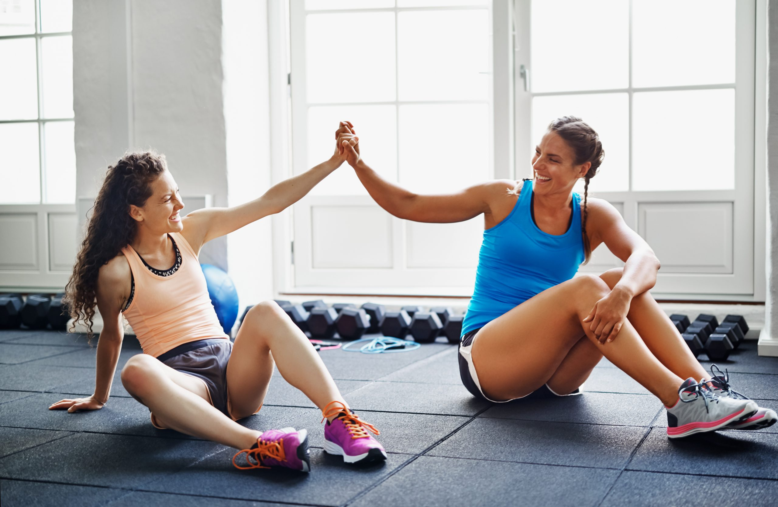 two women giving each other a high five after a workout