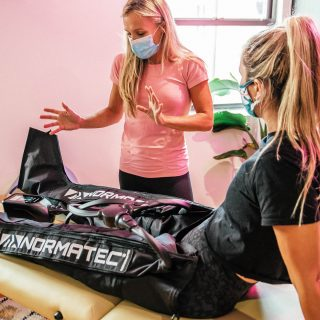a physical therapist talking to a patient wearing normatec boots