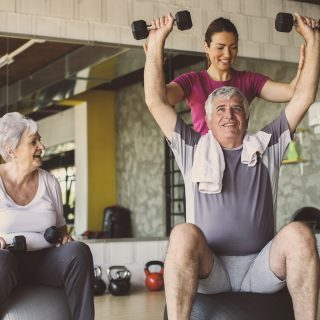 a physical therapist assisting two seniors with strength and conditioning exercises
